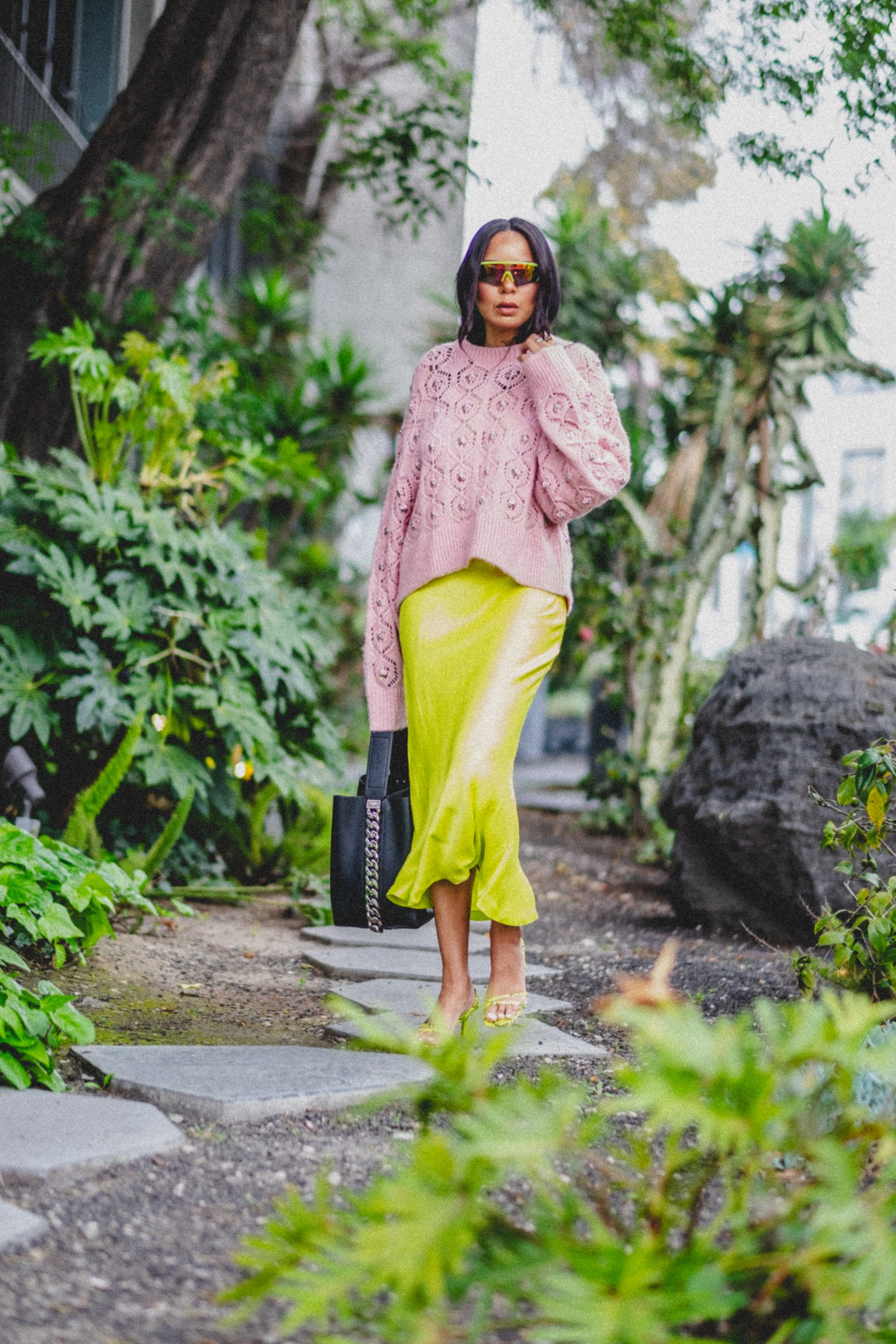 woman with a neon mid calf skirt and pastel pink sweater