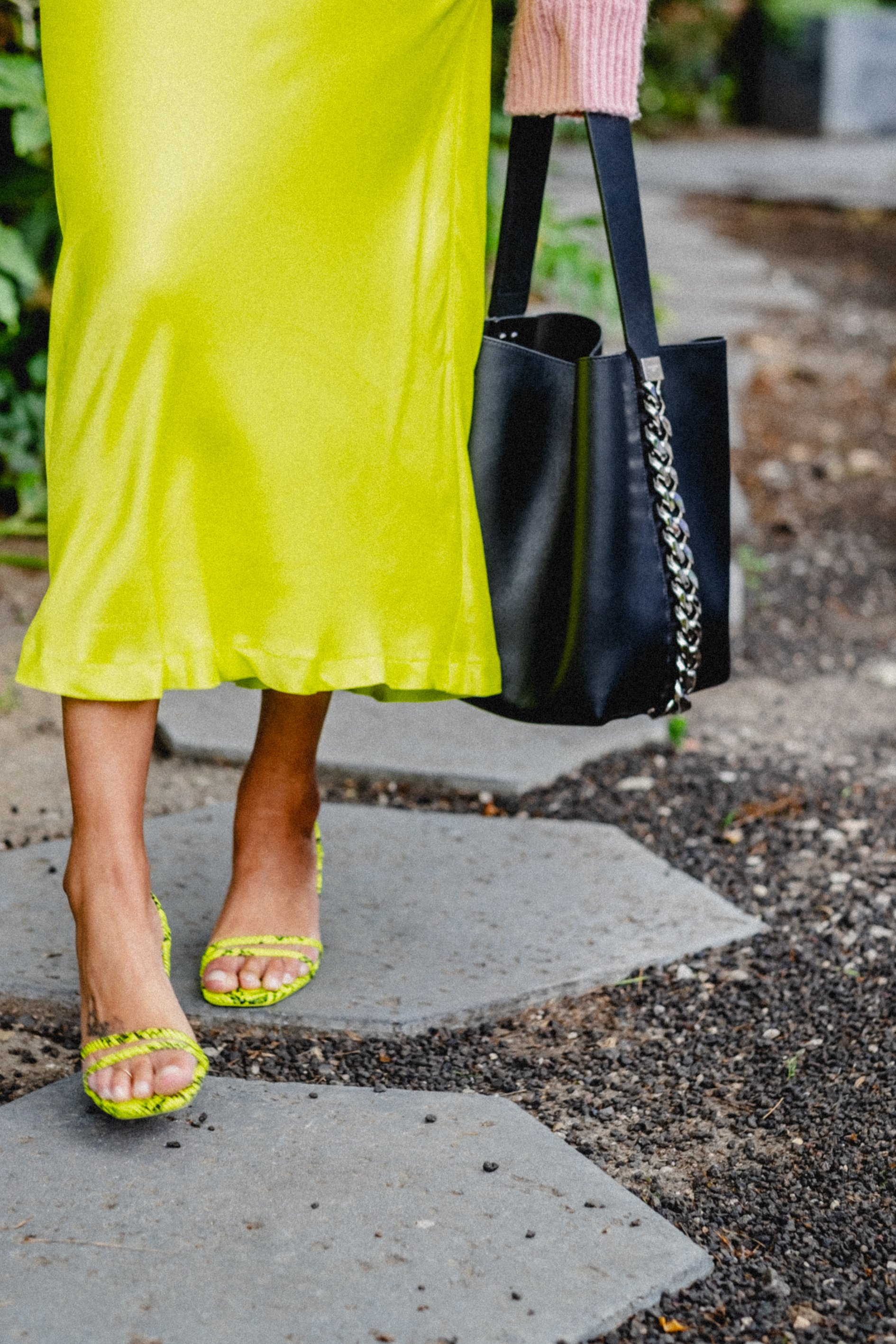 close up of givenchy bag with neon green ankle length skirt and neon strapy sandals